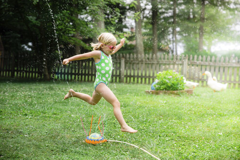 Side view of girl in swimwear running over sprinklers at yard - CAVF55188