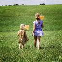 Rear view of sisters walking on grassy field - CAVF55191