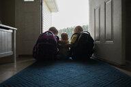 Rear view of siblings sitting at doorway - CAVF55200