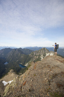 Full length of hiker photographing while standing on cliff against sky - CAVF55263
