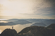 High angle view of hiker with arms raised standing on mountain against cloudy sky during sunset - CAVF55266