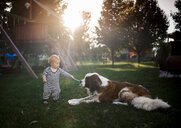Baby boy playing with dog at playground - CAVF55275