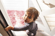 High angle portrait of cute baby boy standing at doorway - CAVF55287