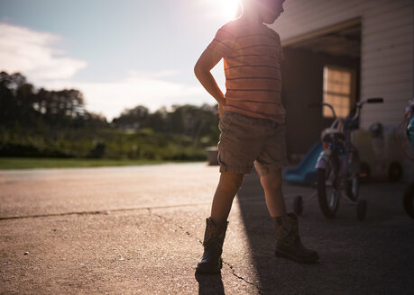 Boy standing at driveway during sunny day - CAVF55314