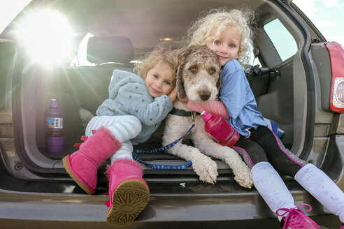 Portrait of smiling sisters embracing dog sitting in car trunk - CAVF55317