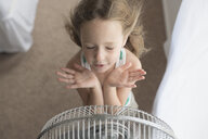High angle view of girl with eyes closed standing in front of windy electric fan - CAVF55320