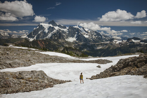 Mid distance view of female hiker standing on snow against mountains and cloudy sky during winter at North Cascades National Park - CAVF55440