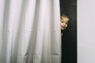 Portrait of smiling boy standing by curtain at home - CAVF55449