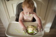 High angle view of baby boy eating cake while sitting on high chair at home during birthday - CAVF55452