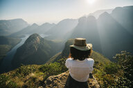 Rear view of woman wearing hat looking at view while sitting on mountain against sky during sunny day - CAVF55467
