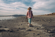 Rear view of girl walking on lakeshore against cloudy sky - CAVF55482