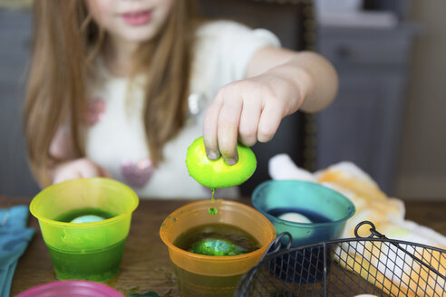 Midsection of girl dipping Easter Egg in dyed water on table at home - CAVF55485