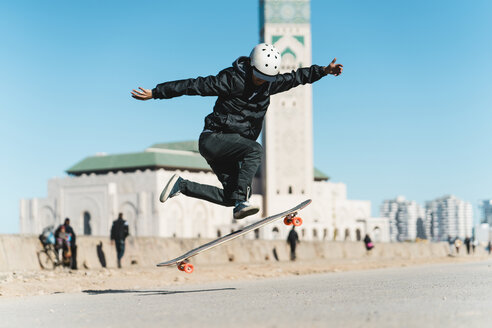 Man performing stunt while skateboarding against Mosque Hassan II - CAVF55494