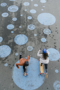 High angle view of friends skateboarding on footpath - CAVF55500