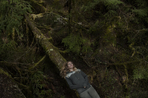 High angle view of thoughtful woman lying on log in forest - CAVF55515