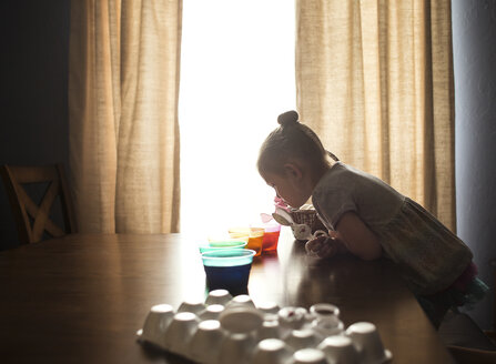 Side view of girl preparing Easter eggs on table at home - CAVF55542