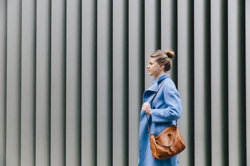 Side view of young woman wearing trench coat while carrying purse against shutter in city - CAVF55551