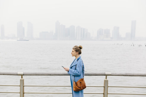 Side view of young woman with purse wearing trench coat while holding smart phone by railing and river in city - CAVF55554