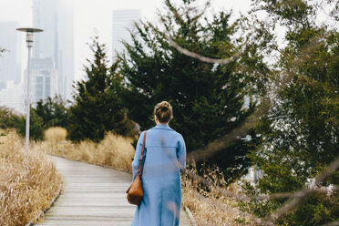 Rear view of young woman with purse wearing trench coat while walking on boardwalk in city - CAVF55557