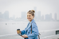 Portrait of cheerful young woman holding disposable cup and smart phone while standing by river in city - CAVF55560