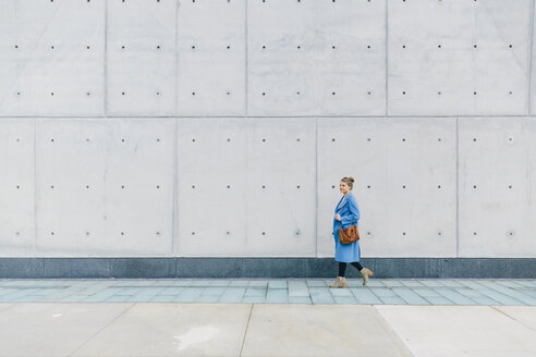 Young woman with purse wearing trench coat while walking against wall in city - CAVF55563