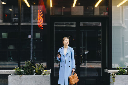Young woman with smart phone and purse wearing trench coat while standing against building's entrance in city - CAVF55566