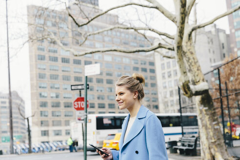 Side view of smiling young woman with smart phone standing on road against buildings in city - CAVF55569