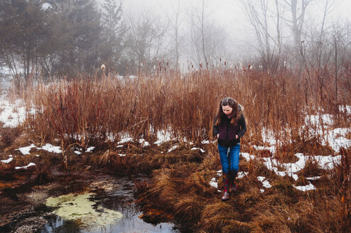 Girl walking on grassy field by lake in forest during winter - CAVF55584