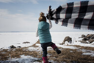 Rear view of girl holding scarf while standing on field by frozen lake against sky - CAVF55602