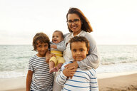 Portrait of smiling mother with children at beach against sea - CAVF55629