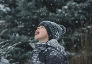 Playful boy sticking out tongue during snowfall - CAVF55647