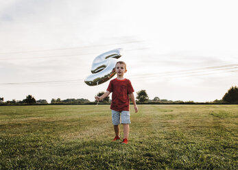 Boy holding number 5 balloon while walking on grassy field against sky - CAVF55689