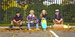 Portrait of friends with skateboards sitting on footpath at park during autumn - CAVF55710