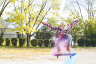 Portrait of man with powder paint jumping while skateboarding at park during autumn - CAVF55713