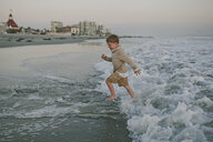 Side view of playful boy running on shore - CAVF55743