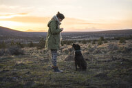 Side view of woman standing by dog on field against sky during sunset - CAVF55755
