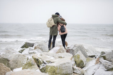 Rear view of couple with backpacks embracing while standing on rocks at beach by sea against clear sky - CAVF55773