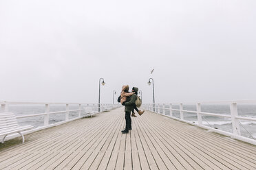 Boyfriend carrying girlfriend while standing on pier against clear sky - CAVF55779