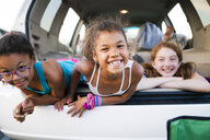Portrait of carefree sisters lying in car trunk with friend - CAVF55809