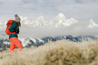 Female hiker with backpack looking at view against snowcapped mountains - CAVF55830