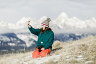 Female hiker taking selfie with smart phone against mountains during winter - CAVF55833