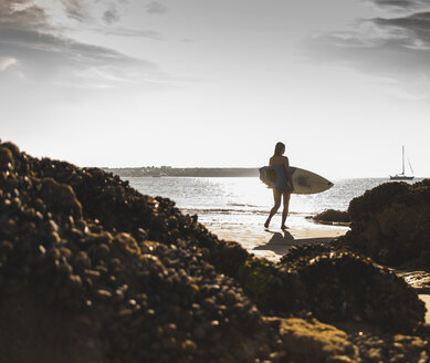 France, Brittany, young woman carrying surfboard on a rocky beach at the sea - UUF15889