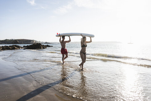 France, Brittany, young couple carrying an SUP board at the sea together - UUF15919