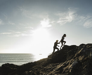 France, Brittany, young couple climbing on a rock at the beach at sunset - UUF15931