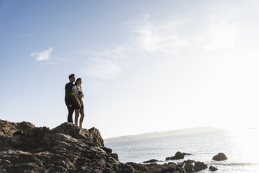 France, Brittany, young couple standing on rock at the beach at sunset - UUF15934