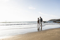 France, Brittany, young couple walking hand in hand at the beach - UUF15940