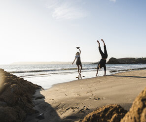 France, Brittany, young man doing a handstand next to girlfriend on the beach - UUF15946