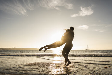 France, Brittany, happy young couple hugging on the beach at sunset - UUF15952