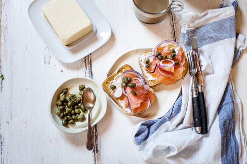 Slices of toast with smoked salmon, caperberries, onion rings, and coffee - SBDF03821