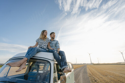 Couple sitting on camper van in rural landscape with wind turbines in background - GUSF01389
